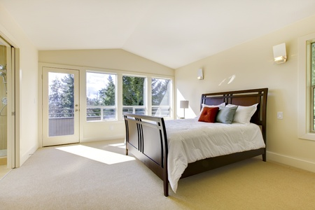 Large bright classic new bedroom interior with beige walls.