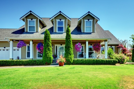 American Country farm luxury house with porch and beautiful flowers. Stock Photo