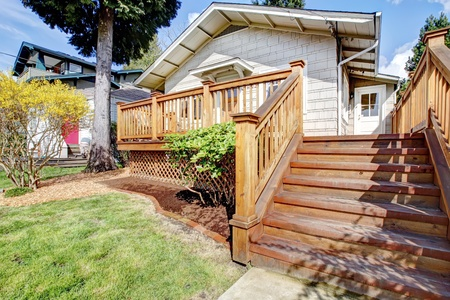 Small white house with wood deck and steps. photo