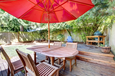 Back yard large deck with red umbrella and chairs and fenced yard. Stock Photo - 13163614