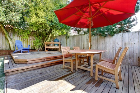 Back yard large deck with red umbrella and chairs. photo