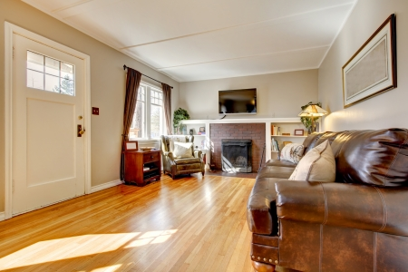 Living room with brown curtain and hardwood floor and leather sofa. photo