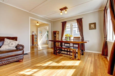 wood molding: Dining room with brown curtain and hardwood floor and leather sofa.