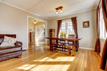 holzboden: Esszimmer mit braunen Vorhang und Parkett und Ledersofa.