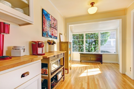 Yellow bright kitchen with large window and bench. photo