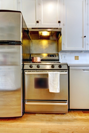 Stove and refrigerator in stainless steal with white kitchen and hardwood floor. photo