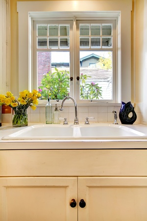 Kitchen double sink and white cabinet with window.