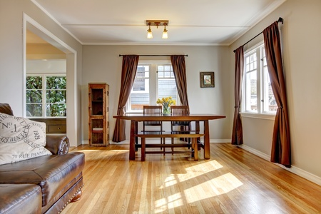 Dining room with brown curtain and hardwood floor and leather sofa. photo