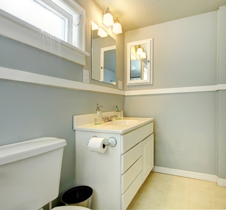 Grey bathroom with white simple cabinet and toilet. photo