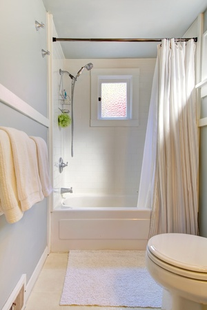 Small blue bathroom with light grey blue and shower curtain. photo