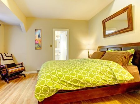 Modern bedroom with bright green bed spread and hardwood floor.
