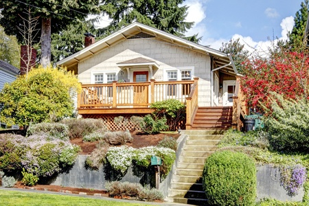 Small white house in the hill with flowers with deck. Stock Photo - 13163656
