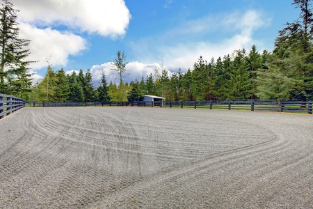 Horse farm gravel open arena with small shed and black fence. Stock Photo - 13294859