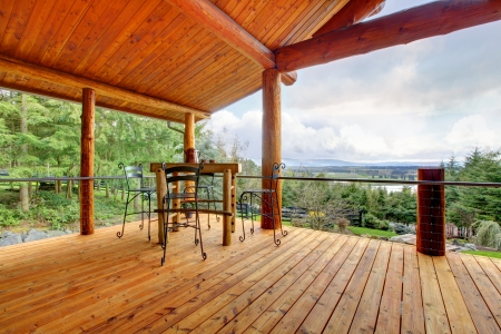 log cabin: Large Porch of the log cabin with small table and forest view. Stock Photo