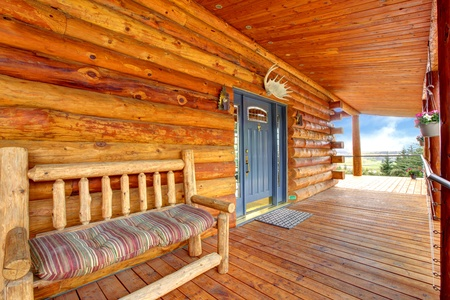 log cabin: Wood log cabinet porch with entrance and bench with firelds view.