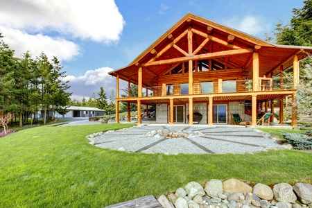 log cabin: Beautiful American classic log cabin with porch and circle fire pit.