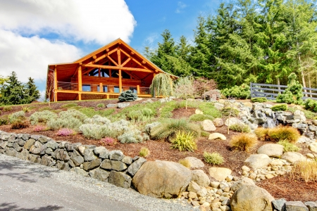 Schönes Blockhaus auf dem Hügel mit Wasserfall und Blumen. Standard-Bild