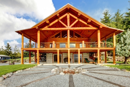 Large log cabin with large porch and fire circle Stock Photo