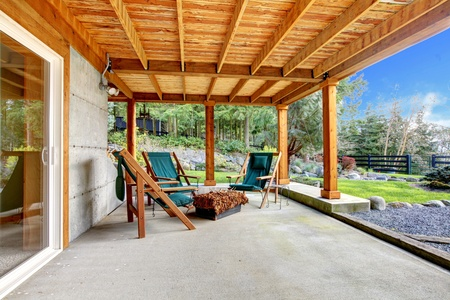 Ground level deck with chairs and door with wood ceiling. photo