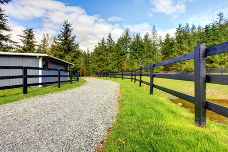 Horse farm with road, fence and shed with green grass. photo
