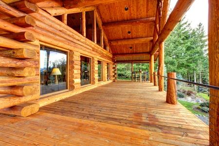 cabaña: Registro de Gabinete de madera porche con entrada y un banco con vista al firelds. Foto de archivo