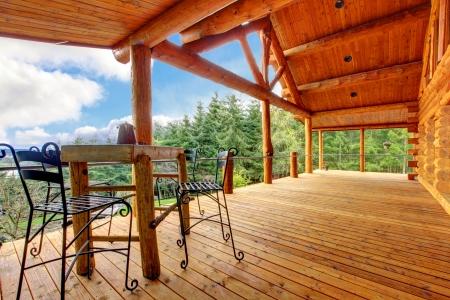 Gran porche de la cabaña de madera con una pequeña mesa y vista al bosque. Foto de archivo