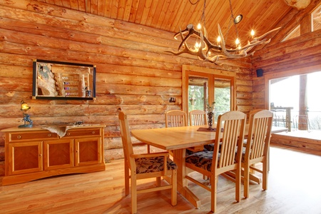 royalty free photo: Log cabin dining room interior with custom furniture.