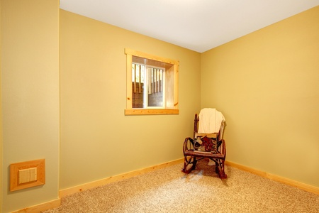 Simple empty basement bedroom with chair and green walls. photo