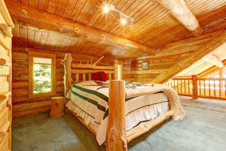 contemporary bedroom: Log cabin bedroom under wood large ceiling with queen size bed.