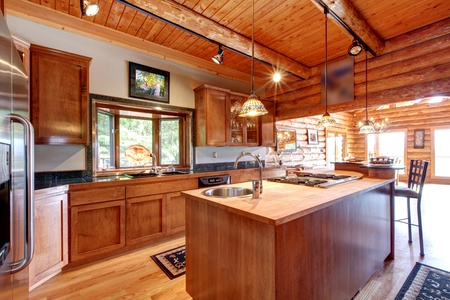 kitchen counter top: Log cabin large kitchen interior with island.