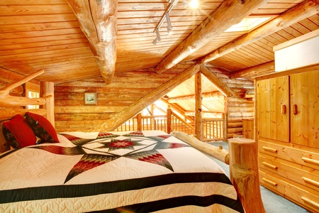 Log cabin bedroom under wood large ceiling with queen size bed. Stock Photo - 13354800