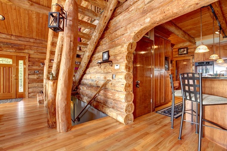 Log cabin kitchen and staircase interior with large wood logs. photo