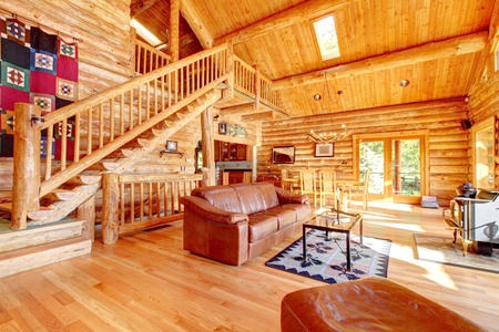 Large luxury log cabin house living room with large staircase. Archivio Fotografico
