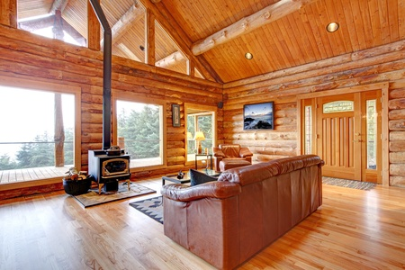 fireplace family: Large luxury log cabin house living room with large windows.