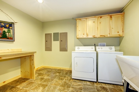 dryer: Laundry roon with sink and folding desk and green walls.