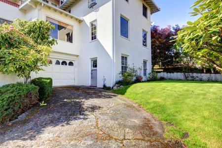 White large white Spanish style house with back yard. photo