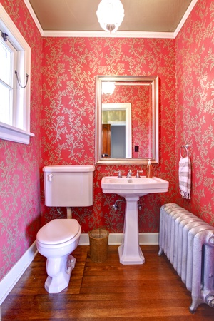 Luxury red and gold small bathroom with silver radiator. Stock Photo