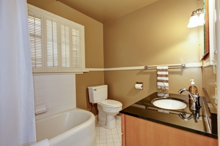 Old brown bathroom with white tub and modern sink. photo