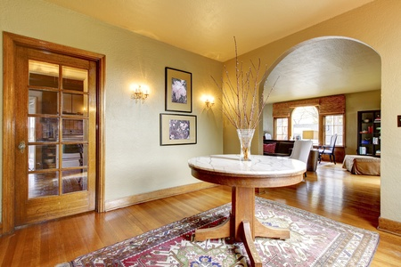 Luxury entrance home interior with round table and hardwood floor. photo