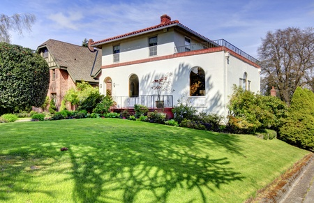 Spanish style white large home front exterior with large green lawn.