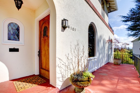 Spanish style white house with red concrete porch and front door.