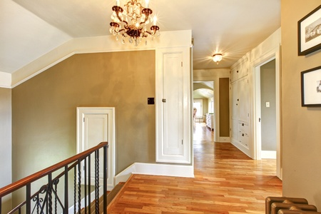 Luxury antique home hallway and staircase with green walls and hardwood floor.
