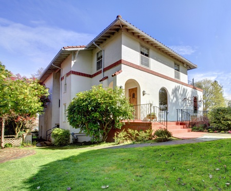 Spanish style white large home front exterior with large green lawn. photo