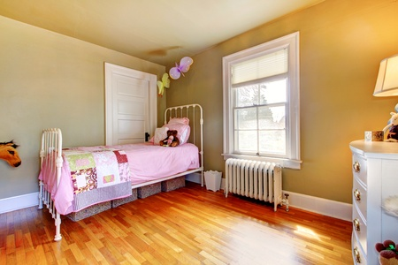 Baby girl bedroom interior with pink bed and hardwood floor. photo