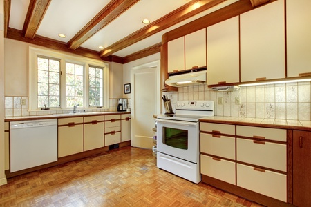 Old simple white and wood kitchen with hardwood floor and white appliances. photo