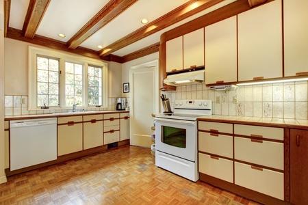 cuisine: Vieux cuisine simple blanc et bois avec plancher de bois franc et des appareils blancs. Banque d'images