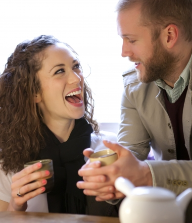 Young beautiful couple drinking tea and laughing. Stock Photo - 13600478