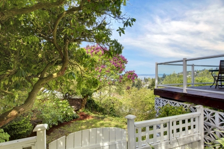 House deck and fence to the back yard with spring trees. photo
