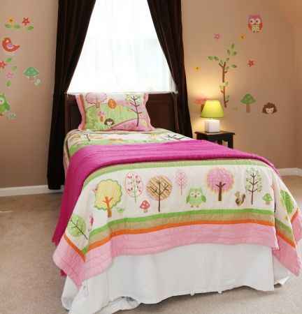 Baby girl kids bedroom interior with pink bed and brown walls. photo