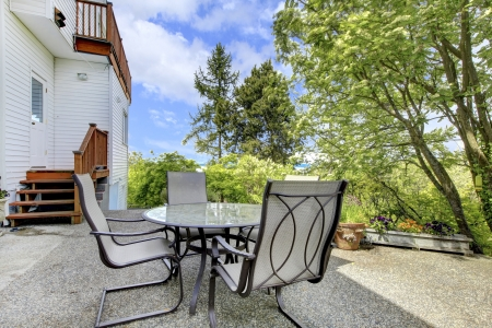 Terrace with outdoor table and chairs in the back yard of the white house. Stock Photo - 13888959
